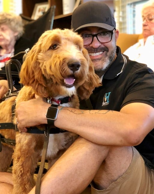 carlos hernandez with goldendoodle service dog